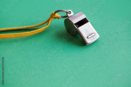 Fotomural  Vintage silver whistle on green paper background
