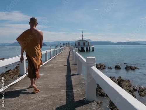 Monaco buddista passeggia lungo il mare Fototapeta