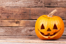 Funny Halloween Pumpkin On Wooden Background. Traditional Halloween Pumpkin And Copy Space. Halloween Symbols And Traditions.
