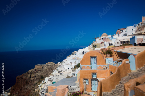 Foto op Plexiglas Santorini Oia town on Santorini island, Greece. Traditional and famous houses and churches with blue domes over the Caldera, Aegean sea (color toned image)