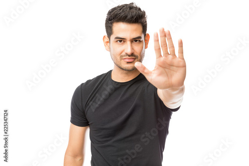 Valokuva  Serious Young Man Making Stop Gesture Against White Background