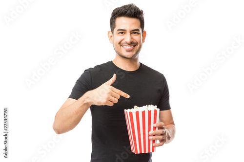Smiling Attractive Male Pointing At Popcorn Bucket