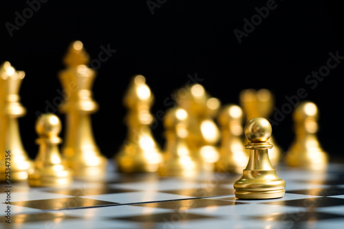 Photo  Gold pawn is on the first move in chess game on black background (Concept for bu