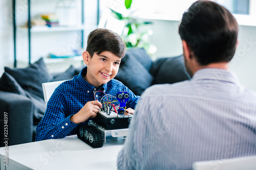 Cheerful smart boy sitting at the table with father