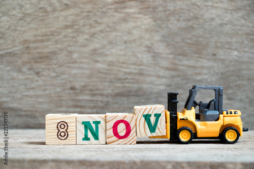 Fényképezés  Toy forklift hold block V to complete word 8nov on wood background (Concept for