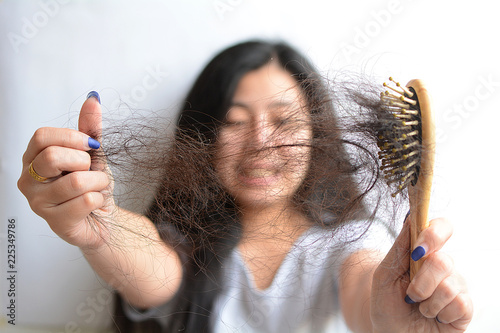 Hair loss, hair fall everyday serious problem, girl with a comb and problem hair on white background Canvas Print