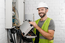 Smiling Electrician Holding To...