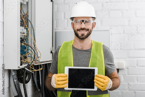 Staande foto Hoogte schaal smiling handsome electrician showing tablet with blank screen near electrical box in corridor