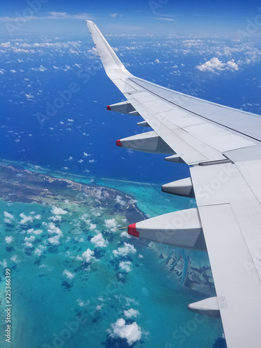 Fotografie, Obraz  Airplane wing view above the Caribbean sea.