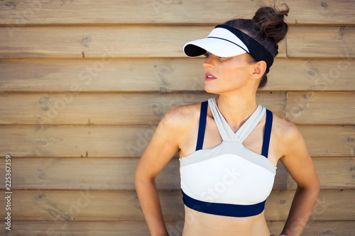 Fotografia  fit woman jogger looking aside against wooden wall