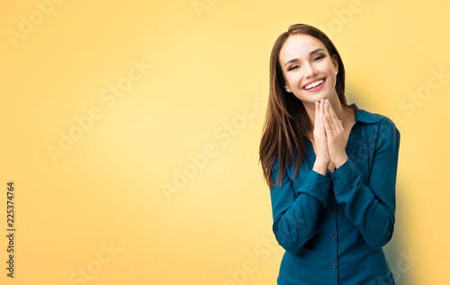 Valokuva  Happy gesturing smiling young woman, over yellow