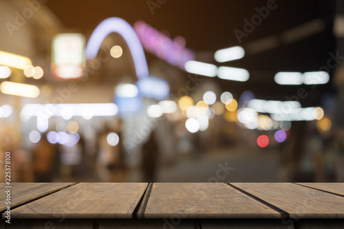 Fotografía  Empty wooden table on front blurred colorful night street background, copy space