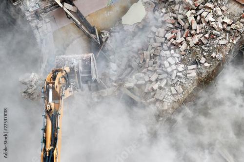 Fototapeta Building demolition with an excavator in dust cloud.