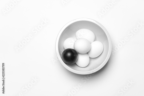 Fotografía  on a white background, white eggs and one black symbolizing diversity, separatio