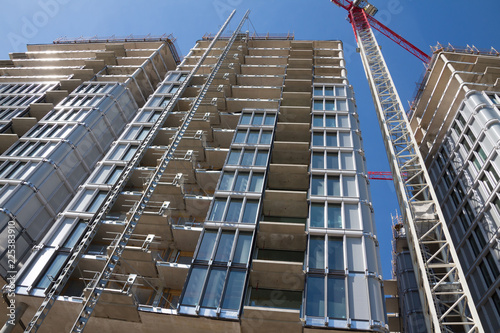 Poster London High-rise building under construction. The site with cranes against blue sky