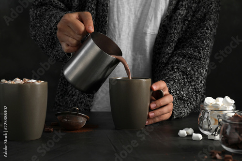 Foto op Plexiglas Chocolade Woman pouring hot chocolate with milk into cup on table, closeup
