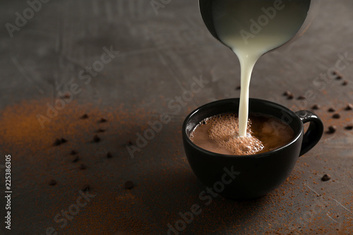 Montage in der Fensternische Schokolade Pouring milk into cup with tasty hot chocolate on table. Space for text