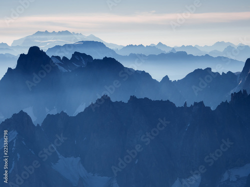 Foto op Aluminium Nachtblauw Early morning Alpine landscape with rows of steep peaks