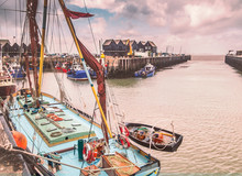 Fishing Boats And Huts In Whitstable Harbour, Kent, UK. A Small Wooden Rowing  Boat Can Be Seen Hanging Off The Side On The Thames Barge In The Foreground