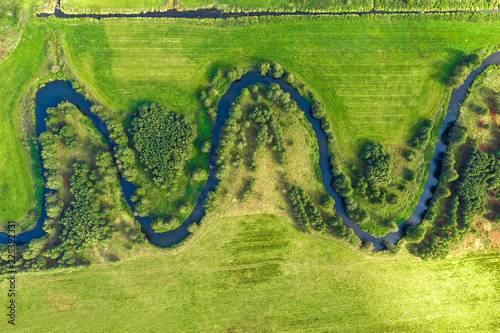 Aerial view on winding river in rural landscape