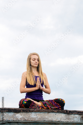 woman in a lotus pose on the roof