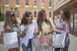 Gorgeous and attractive women with stylish and fashionable shopping bags walking through town, shopping with friends