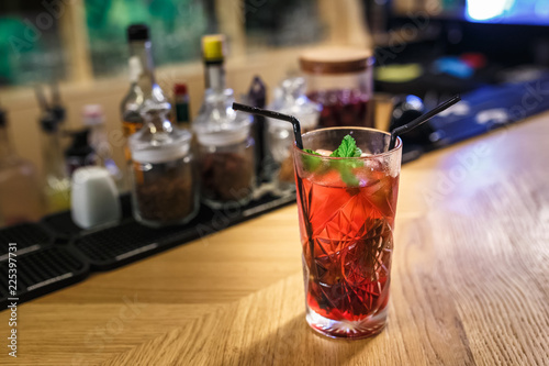 red cocktail in a glass with mint and two tubes on a table in a luxury bar