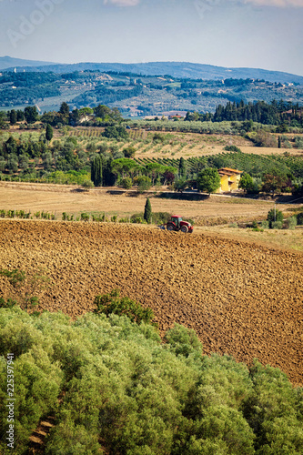 Typical Tuscan hill landscape with vineyards, olive grove and tractor working.