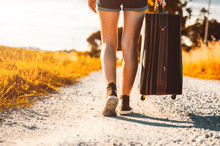 Close Up Of Legs Of A Woman At Vacation Walking On The Road Holding Her Suitcase On A Countryside Background