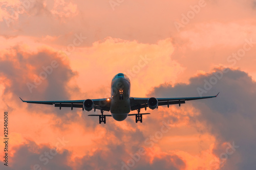 Tuinposter Vliegtuig Commercial airplane flying runway airport above dramatic clouds.