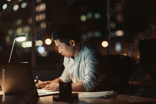 Fototapeta  Asian businessman working at his desk late into the evening