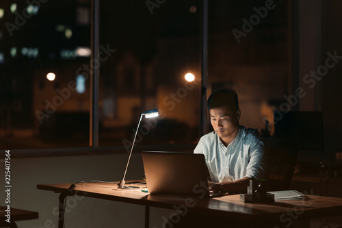 Foto  Asian businessman working alone in a dark office at night
