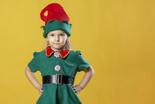 A Little Girl In The Costume Of A Christmas Elf Rests Her Hands On Her Hips. Near The Blank Place For Text, Copy Space.