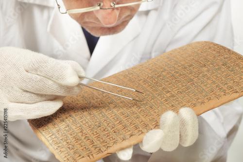 Obraz na płótnie Scientist exploring ancient type of Akkad empire style cuneiform with tweezers