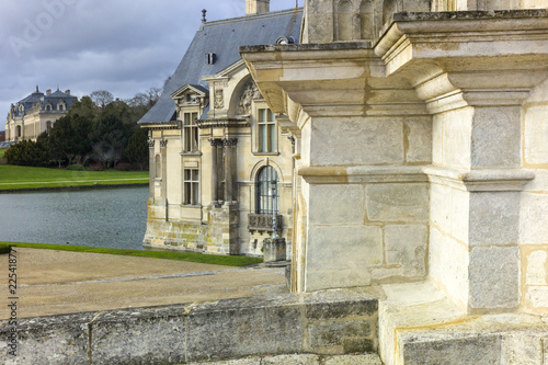 Spoed Foto op Canvas Oude gebouw Detail of Palace of Chantilly in golden afternoon light with moat and distant gallery