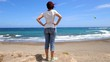 Woman standing on a rock at the seaside and looking at the windsurfers and kite surfers, slow-motion