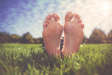 Shallow DOF On A Man With His  Feet Crossed In A Park On A Hot Summer Day