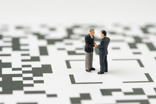Negotiation, Discussion For Solution Of Problems Or Business Partnership Deal Concept, Miniature Figurine Businessmen Handshaking And Standing At The Center Of QR Code Consumer And Commerce Symbol