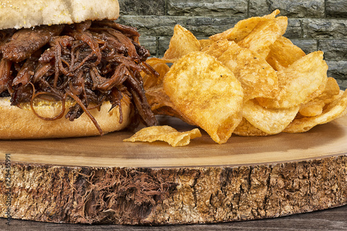 Close up on pulled pork sandwich and potato chips. Wall of bricks in background.