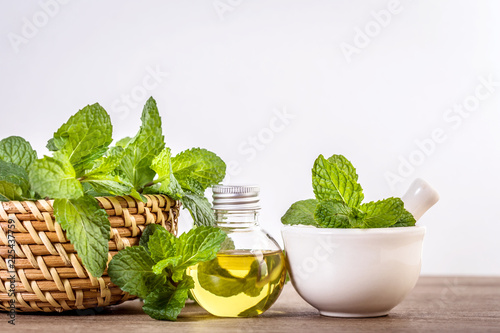 Obraz Aroma essential oil from a peppermint in the bottle on the table with fresh green mint leaf - fototapety do salonu
