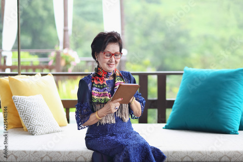 Photographie  asian senior woman sitting on the sofa and using a tablet