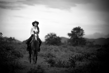 cowgirl  riding on a mountain with an Black and white tone the cowgirl  riding on a mountain with an yellow sky; Concept of friendly  and of summer vacation.