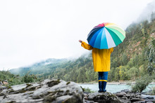 Person Holding A Colored Umbrella. Rainy And Wet Weather.