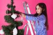 Leinwandbild Motiv Children, holidays and christmas concept - little girl decorating christmas tree on pink background