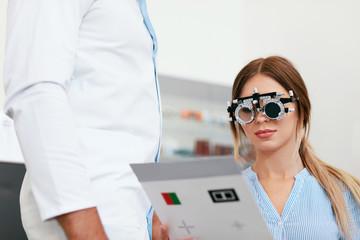 Obraz na Plexi Eye Exam. Woman In Optometry Glasses Reading Eye Test Card