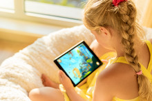 Girl Playing Game On Tablet Co...