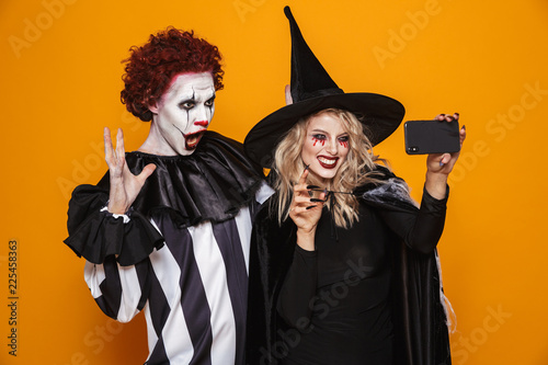 Fotomural Happy witch and clown making selfie on smartphone isolated