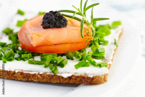 Canape with smoked salmon, soft cheese, tomato and caviar. Symbolic image. Concept for a tasty and healthy meal. Food background. White background. Close up.