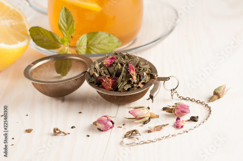 Fotografía  Closeup of cup of tea with tea leaves, mint on vintage wooden background