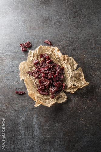 A pile of dried beef jerky pieces on paper and cutting board